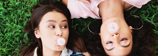 Bild von zwei im Gras liegenden Mädchen