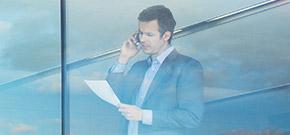 Mann im Anzug steht telefonierend am Fenster eines Bürogebäudes